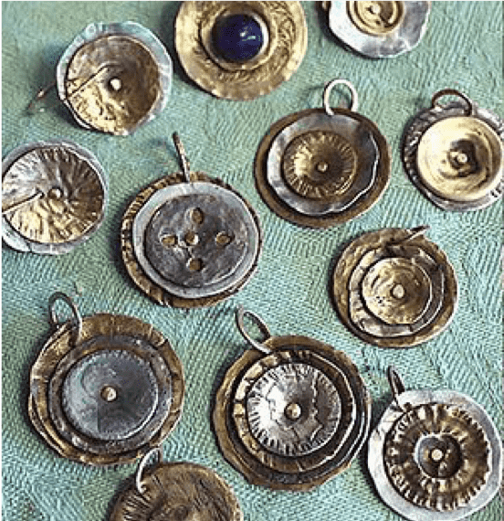 Several pendants, as examples of the work done in this class.  Each piece consists of two to 3 layers of metal fused together.