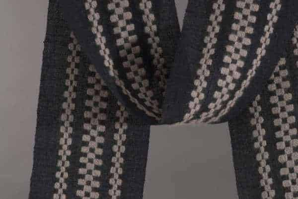 detail of handwoven scarf with three monks belt stripes is an example of supplemental warp