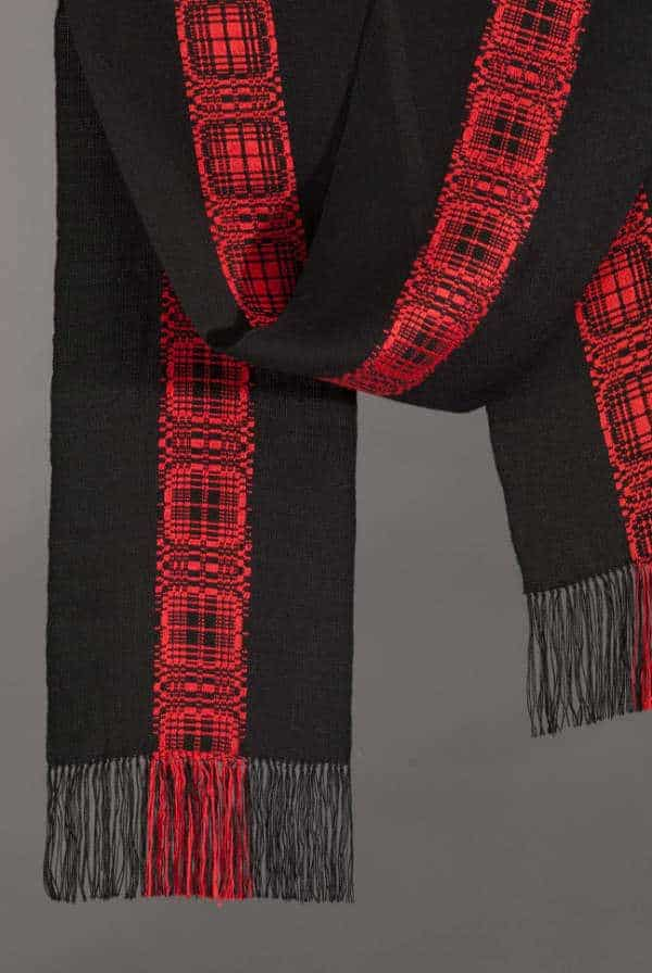 close up of handwoven scarf with a central plaid stripe is an example of supplemental warp