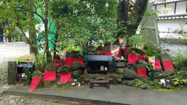 Two small altars surrounded by red flags and vases of flowers in Japan